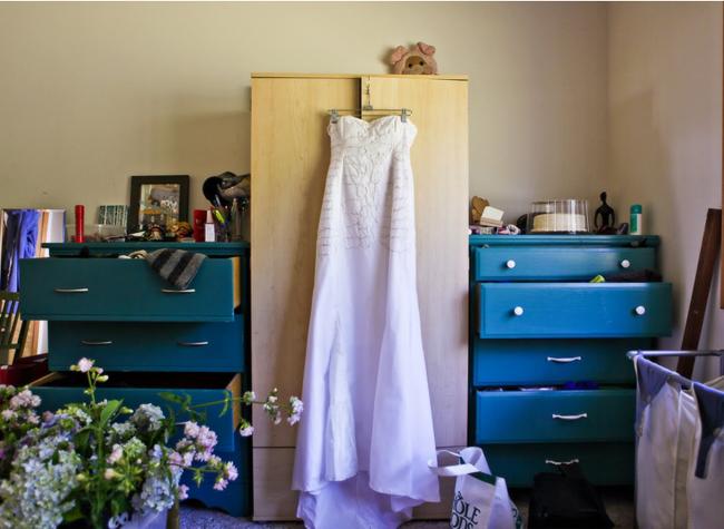 white strapless vegan wedding dress hanging on wardrobe