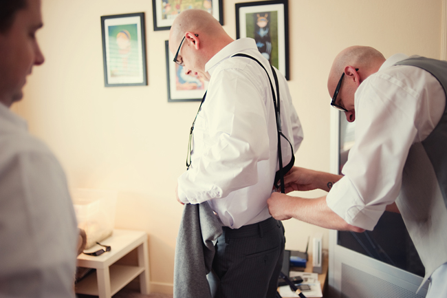 groom putting suspenders on his groomsman