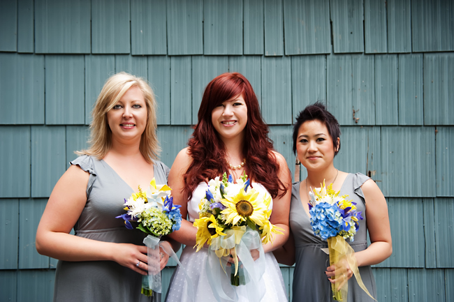 bride and bridesmaids holding bouquets with blue-gray wood backdrop