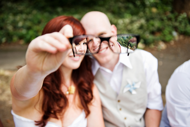 looking through groom's glasses at happy couple