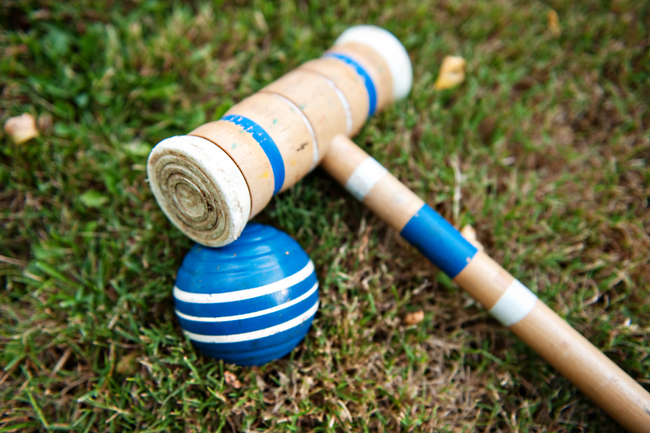 blue ball and croquet mallet on grass