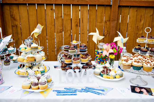 dessert table with cupcakes, pinwheels, and sign
