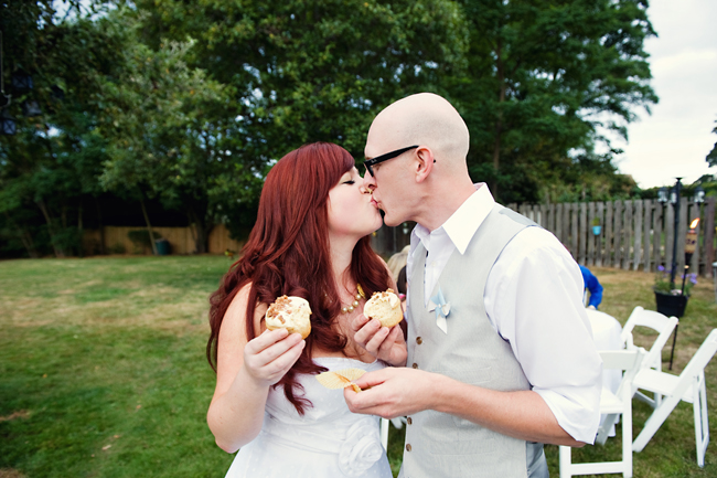 bride and groom kiss while eating cupcakes in backyard