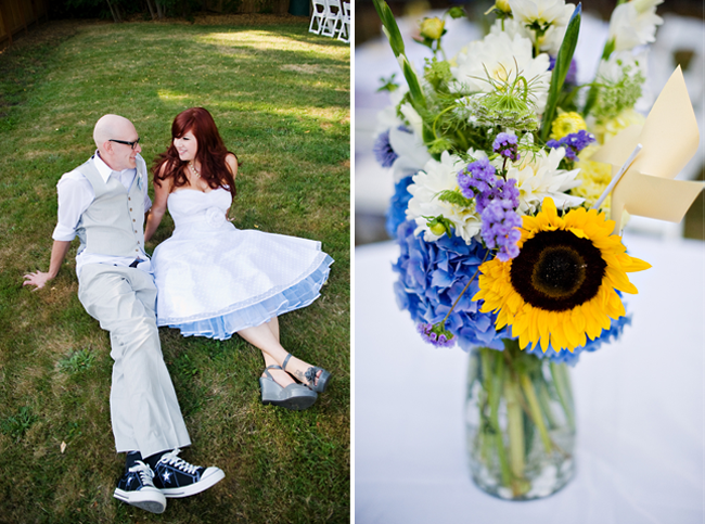 Allison and Corey sit on grass; sunflower and blue hydrangea flower vase