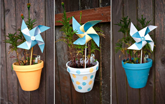plants in pots attached to fence with blue and white pinwheels