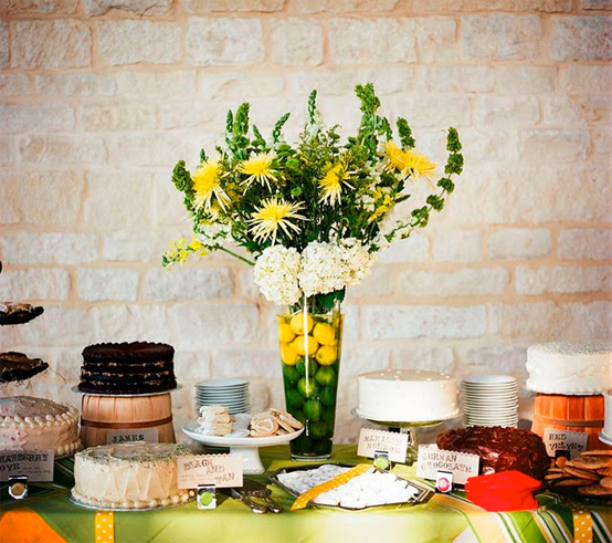 lemons and limes in glass vase surrounded by cakes on dessert table