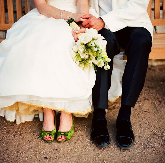 bride and groom sit on bench and hold hands
