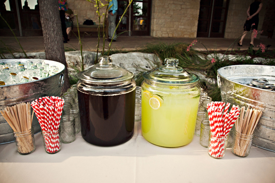 jugs of lemonade with straws and galvanized buckets filled with pop bottles and ice