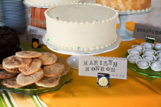 "white cake with sign that says, ""Marilyn Monroe"", plate of cookies next to it"