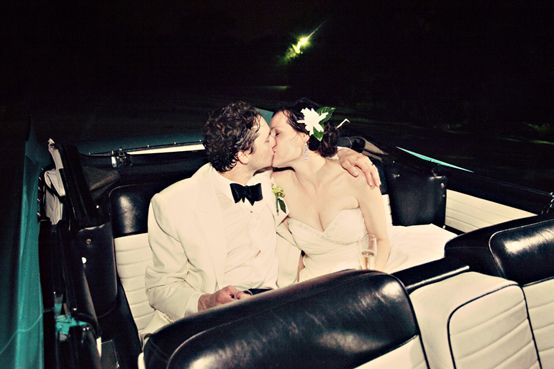 bride and groom kiss in back seat of vintage car