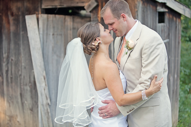 newlyweds touch nose to nose in front of old wooden shed