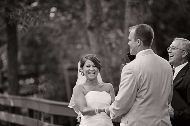 black and white photo of bride and groom laughing at ceremony