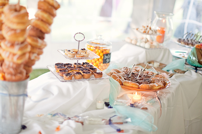 dessert table with donuts, tarts, and candy