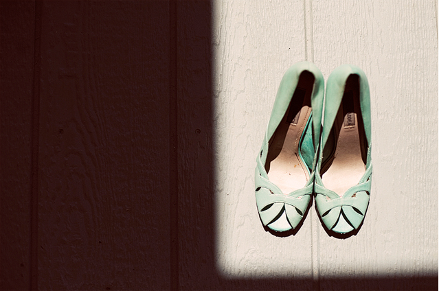 A pair of mint green flat shoes on board floors with sunshine