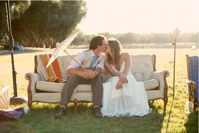 Bride and groom kiss seated on outdoor furniture at The Farm on Putah Creek