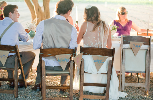 bride and groom sitting on foldup chairs with chairback bunting burlap name cards