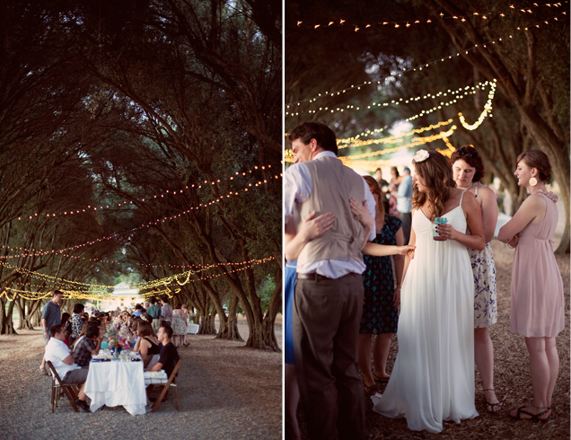 lights strung across a canopy of trees with wedding reception below