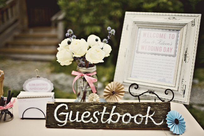 wood guestbook sign on table with framed welcome picture