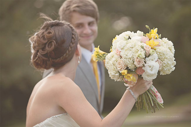bride holding bouquet of hydrangia, roses, yellow freesia, and wildflowers