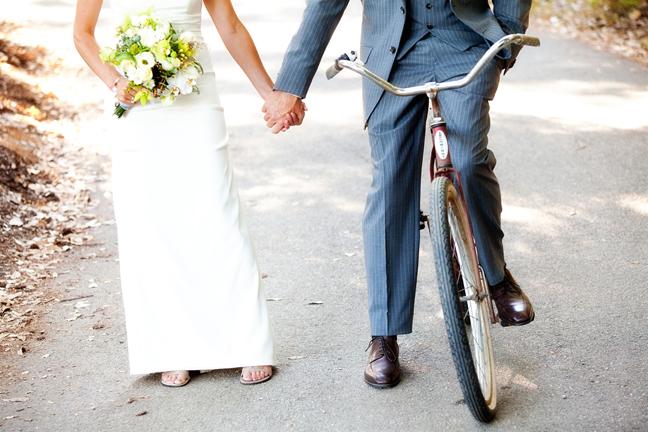 groom on old bike holding brides hand