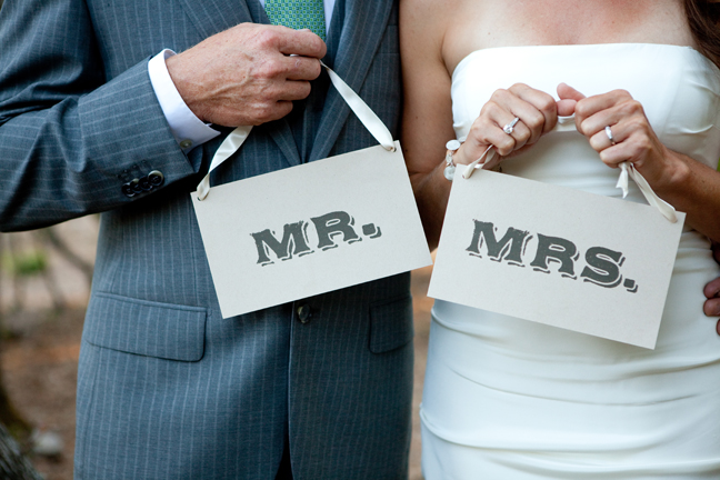 newlyweds holding Mr and Mrs sign
