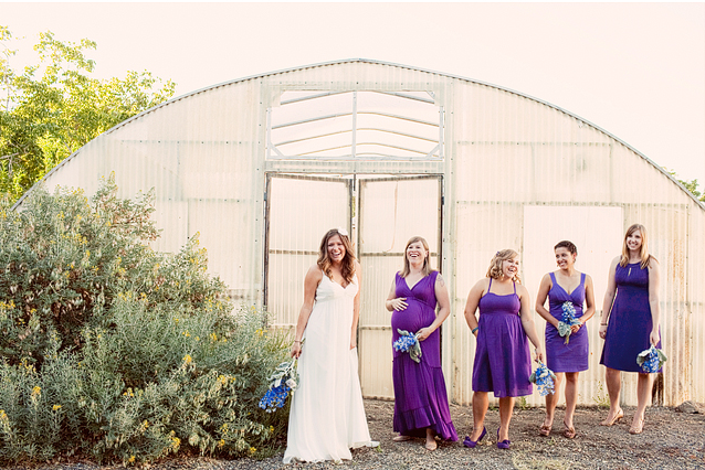 bride with bridesmaids in puple dresses in front of greenhouse