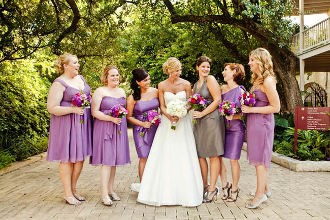 bride in strapless gown and bridesmaids in purple dresses