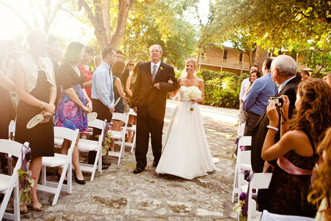 bride and father walk down the stone paved outdoor aisle