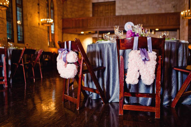 pink tissue paper monogram letters hang on bride and groom chairs