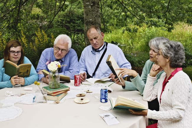 wedding guests sitting outdoors reading old books