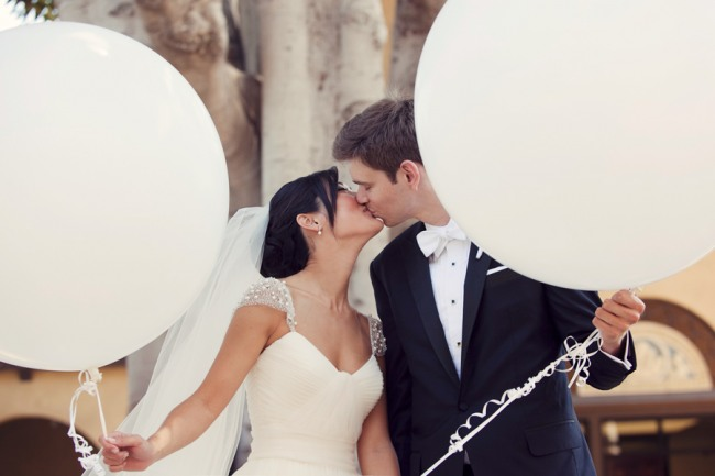 Newlyweds kiss holding white geronimo balloons