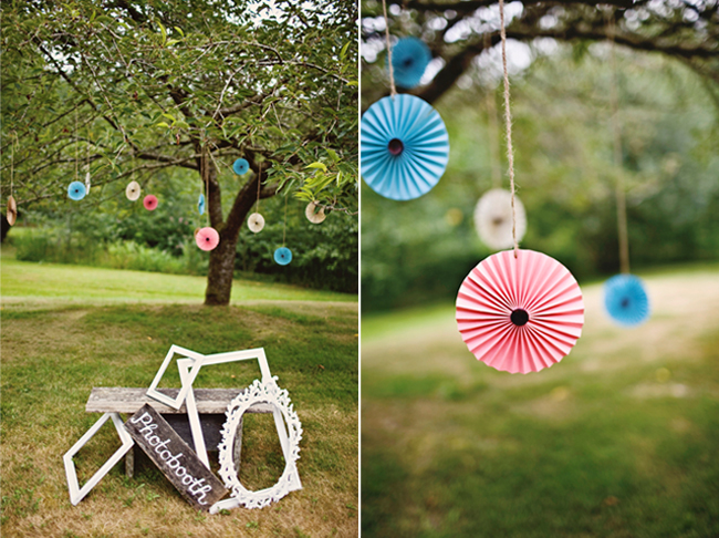 outdoor photobooth with paper pinwheels hanging from tree