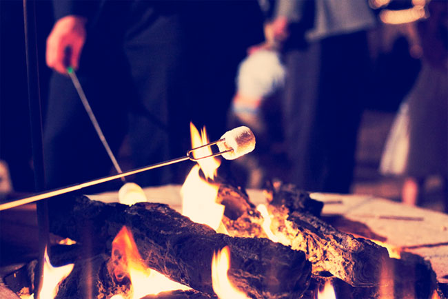 roasting s'mores over campfire at Colorado ranch wedding reception