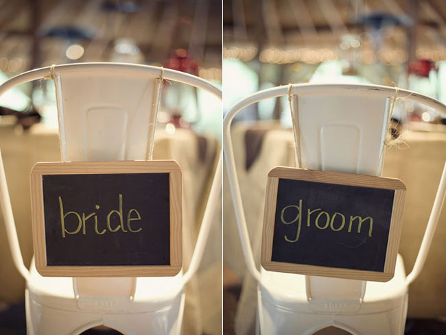 chalkboard signs for bride and groom on back of their chairs