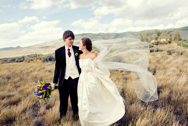 bride and groom roaming the fields of Mountain Meadows Ranch
