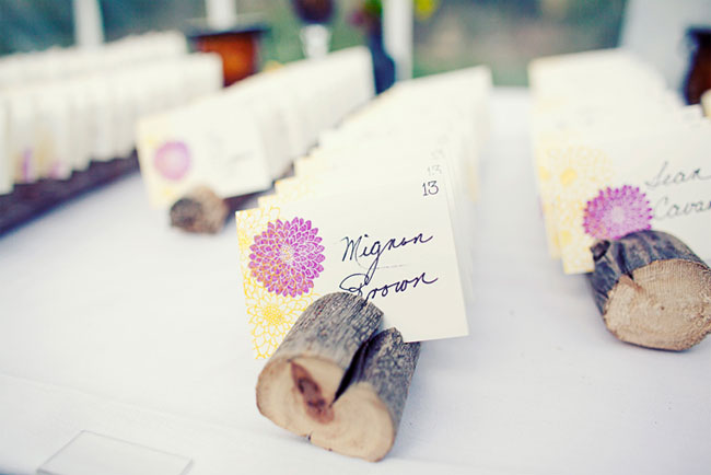 dark purple wedding theme guest seating cards in wood logs
