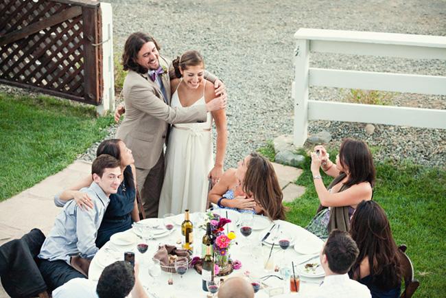 Bride and groom hug while talking to guests at Anvil Vineyard & Ranch wedding