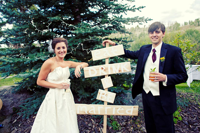 bride and groom enjoying a drink next to DIY sign