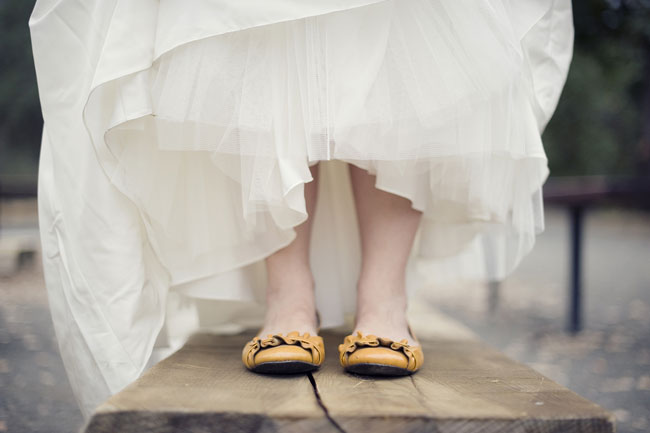 Bride in orange flat shoes standing on wood plank
