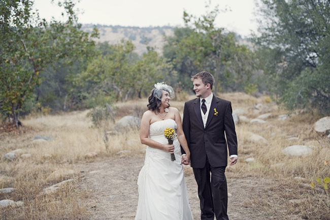 bride and groom hold hands in country setting at River Ridge Ranch wedding