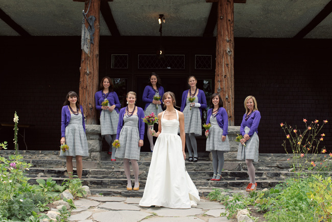 bride and seven bridesmaids with purple cardigans wearing multi-colored shoes