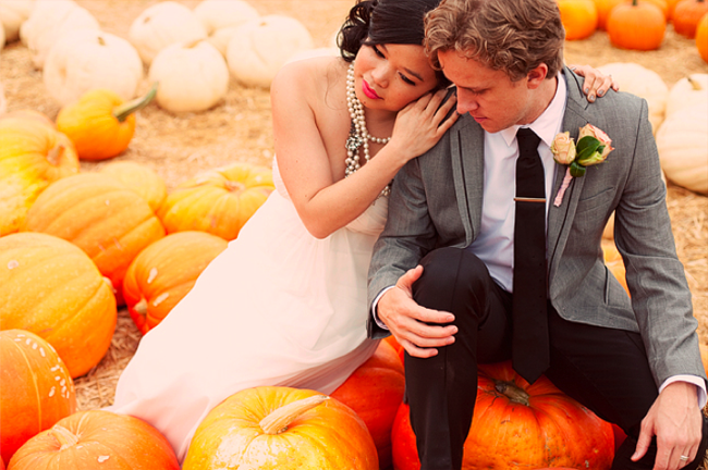 Bride and groom seated on large pumpkins