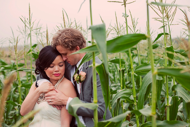 bride and groom embrace in corn field