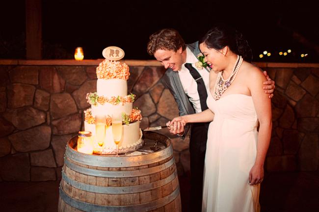 bride and groom cutting cake sitting on wine barrel