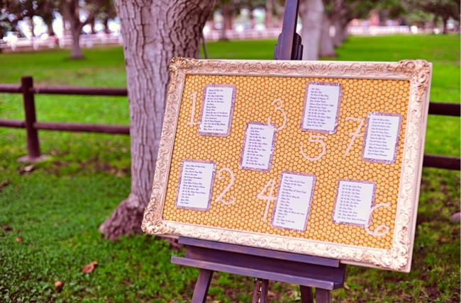 gold framed seating chart on easel