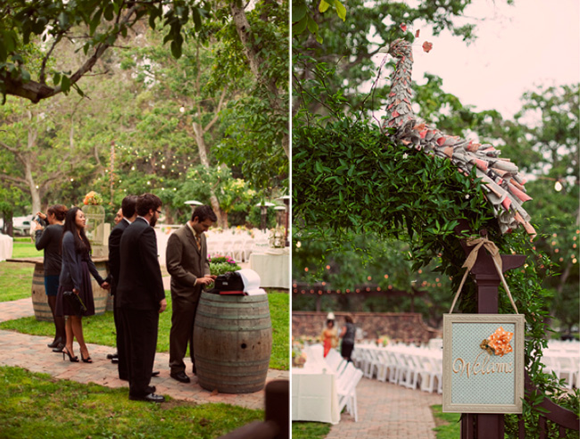 Guest signing guestbook on top of wine barrel using vintage typewriter