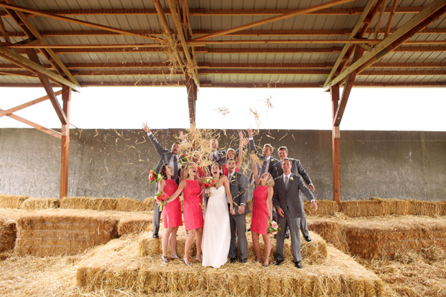 Bridal party standing on haystacks throwing hay at Swans Trail Farms