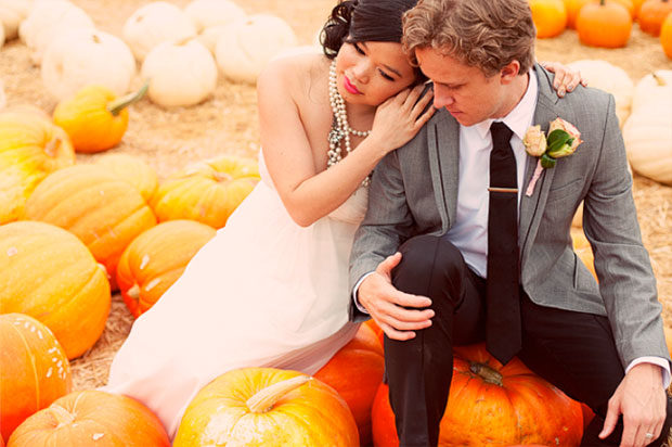 Bride and groom sitting on pumpkins in a pumpkin patch