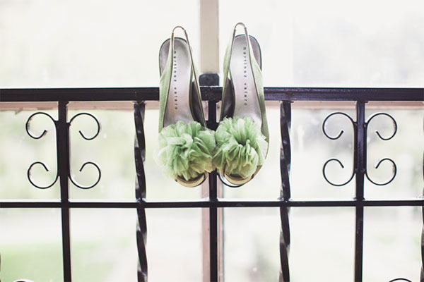 Green wedding shoes with giant green pompoms, hanging from iron railing