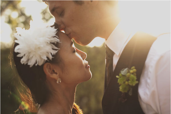 bride and groom embrace in sunset backlight